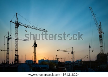 Industrial landscape with silhouettes of cranes on the sunset background stock photo