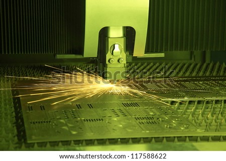Industrial laser cutter with green background, with sparks