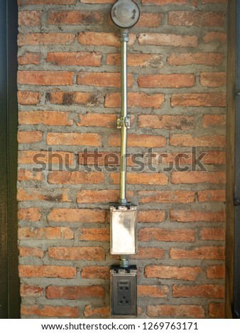 Industrial loft style power outlet set with safety cover installed on naked and roughly brick wall.