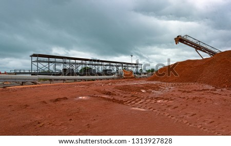 Industrial machinery for transhipment of bauxite ore from mining trains to bulk carrier ships. Kamsar, Guinea.