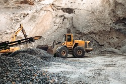 Industrial machinery on ore quarry site, heavy duty excavator moving gravel and rocks. Loading dumper trucks and rock crusher
