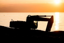 Industrial machinery working at beach in sunset