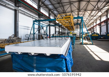 Industrial manufactory workshop for thermal insulation sandwich panel production line for construction. Modern manufacturing storage with machine tools, roller conveyor, factory interior inside #1076195942