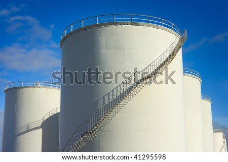 industrial metal white fuel tanks with stairs and blue sky
