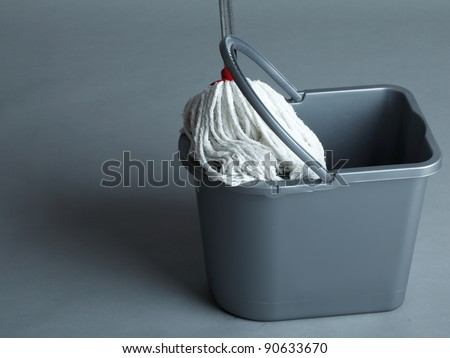 Industrial mop and bucket on grey background