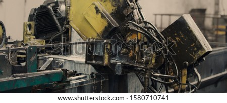 Industrial operating automated machine line for cutting metal profiles in manufacturing process at plant or factory. Concept for metalwork production.