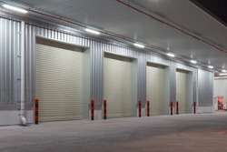 Industrial or commercial building exterior. Use as factory, warehouse, store and workplace. Safety and protection with roller door, roller shutter or overhead door. Concrete pavement floor outside.