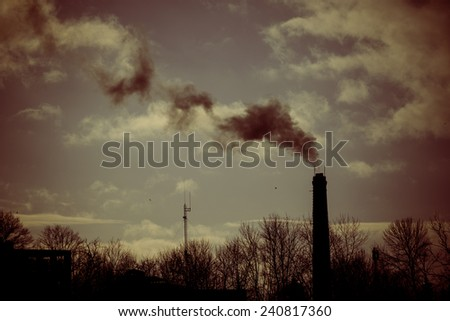 industrial park with chimney and white smoke on blue sky - retro vintage look