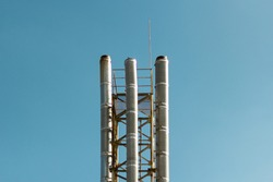 Industrial pipes on a background of blue sky. Metal pipes. Three metal pipes.
