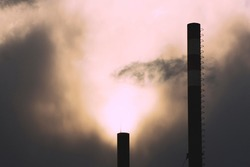 Industrial pipes on dark sunny sky background