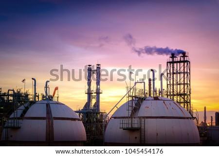 Industrial plant on sky sunset background, Gas storage sphere tank in petrochemical plant with smoke stacks at evening time #1045454176