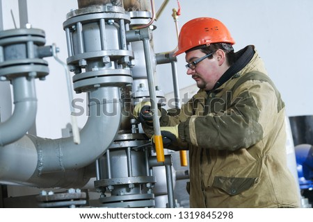 industrial plumber assembling pipes, valves, faucets in water circulation room