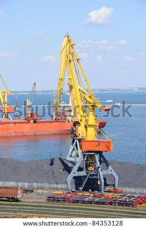 Industrial port with cargo. Coal, tubes, ship, cranes. Railroad and car.