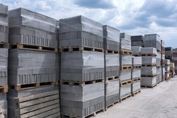 Industrial production of building cement pressed materials. High quality hollow concrete block or cement brick and paving stones. Finished products on pallets packed in film are waiting to be shipped.