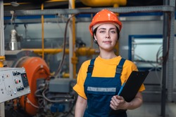 Industrial production. Portrait of a young Caucasian woman in uniform and helmet with a folder in her hand. In the background, boiler equipment. The concept of gender equality.