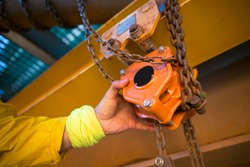 Industrial rigger rope access inspector worker hand commencing safety daily inspection on lifting hoist chain block prior to use on construction site