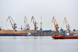 industrial river waterscape with cargo terminal and mooring tugboats and bulk barges