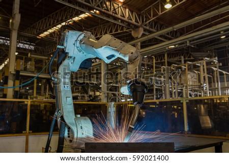Industrial robot is welding metal part in car factory
