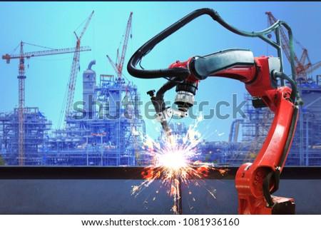 Industrial robot welder welding i beam steel structure construction by metal arc welding against industrial factory site in sunset #1081936160