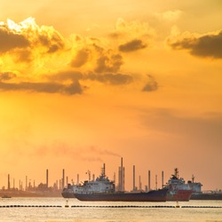 Industrial ships in front of refinery and heavy industry in the sunset. Environment pollution issue.