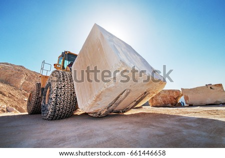 Industrial shot illustrating the production of marble. A bulldozer moving a huge marble block at a quarry.\n \n\n