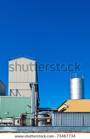 Industrial site with silver silo and cladding buildings - stock photo