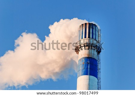 industrial smoke from chimney on blue sky