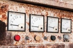 Industrial square ammeters in a row mounted in grungy old control panel, close up photo with selective soft focus