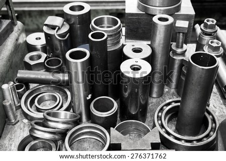 Industrial steel cylinders, pistons and tools in workshop. Industry theme.