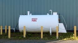 Industrial steel fuel storage tank with bollard barriers