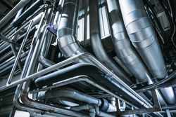 Industrial steel pipes or tubes of air ventilation system as abstract industry equipment background in blue tones