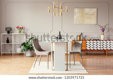 Industrial style, golden pendant light above an exceptional marble table in a trendy dining room interior with eclectic decor