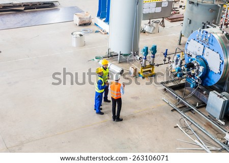 Industrial team of Worker and engineer discussing at machine in factory