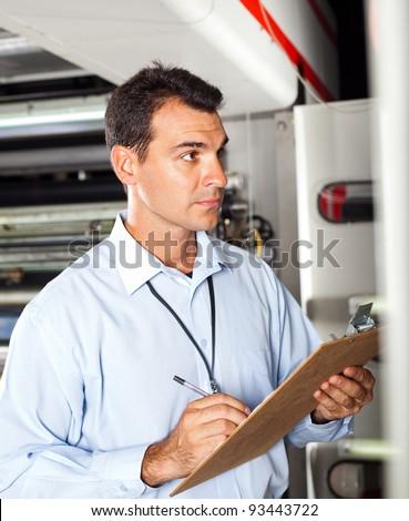 industrial technician taking machine readings