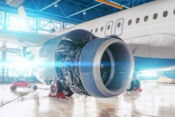 Industrial theme, repair and maintenance of aircraft jet engine with hood open on the wing