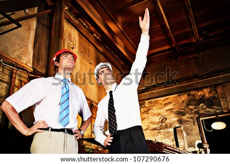 Industrial theme: two engineers at a manufacturing area. - stock photo