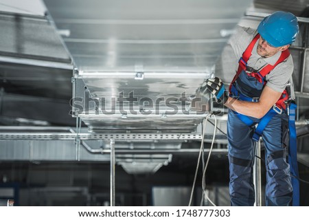 Industrial Theme. Warehouse Heating and Cooling System Installation by Professional Caucasian Technician. Commercial Building Ventilation Rectangle Canals. Air Distribution. Foto stock ©