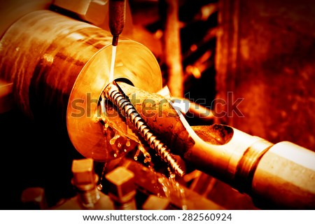 Industrial turning, threading machine at work close-up. Industry concept, red tone.