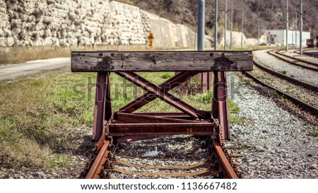Industrial view of dead end railway track. Wooden sign at the end of the rail trail. Concept for end,border and limitation. Foto stock ©