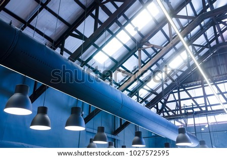 Industrial warehouse interior of roof ceiling structure skylights with ventilation air ducts and pendant lamps