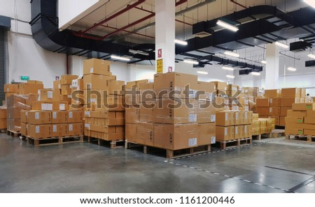 Industrial warehouse interior with shelves and cartons on pallets *Barcode and label on cartons have been blurred*