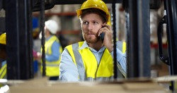 Industrial warehouse manager sitting in forklift truck and having phone call. Portrait of handsome forklift driver having mobile phone conversation in factory storehouse