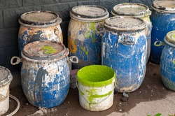 Industrial Waste, Plastic barrels of paint. High Angle View Of Liquids In Containers Against Wall. Dirty containers with stains of dye. Barrel covered with multicolored spots.