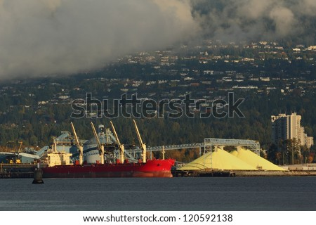 Industrial Waterfront Sulphur Piles, Port of Vancouver. Large yellow piles of sulphur, extracted from natural gas, are ready for shipping. North Vancouver, British Columbia, Canada.