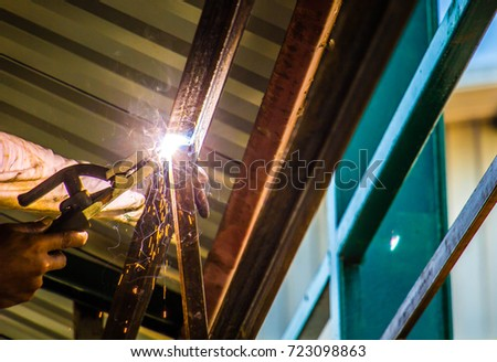 Industrial welder in a small factory #723098863