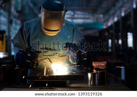 Industrial welder is welding metal part in the factory. #1393119326