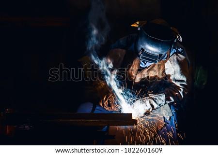 Industrial welder welding fabricated construction in factory, Welding process by Shielded Metal Arc Welding (SMAW) or Stick Welding. Photo stock ©