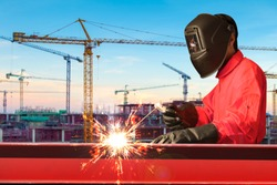 Industrial welder welding i beam steel structure construction by metal arc welding against construction site in sunset
