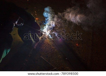 Industrial welder worker holding welding torch during perform welding sheet metal steel plate in construction factory by wearing heat protection gloves with smoke, spark, arc, fire, flash, hot #789398500