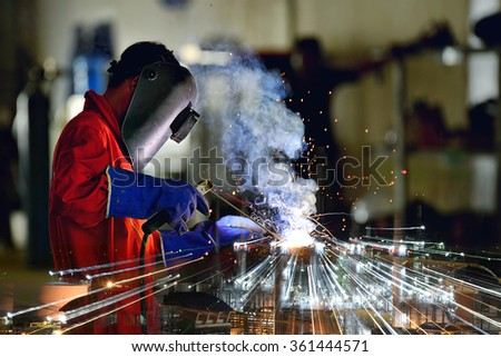 Industrial Worker at the factory welding close up